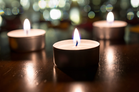 3 Romantic Tea Lights For Dinner On Wooden Table With Bokeh At Night Stock Photo