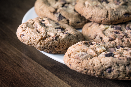 Several Chocolate Cookies Lying On The Edge Of A White Plate On A Wooden Vintage Table