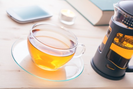 A Cup Of Tea With Teapot, Smartphone, Candle And A Book