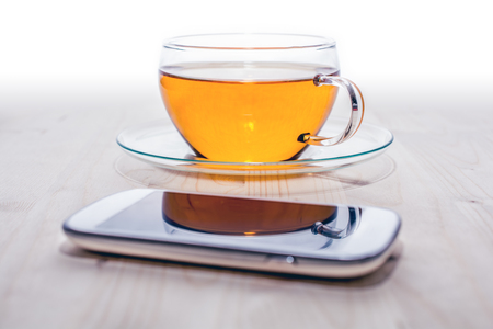 A Smartphone In Front Of A Cup Of Tea On A Wooden Board Stok Fotoğraf