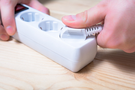 Pulling An Electrical Plug Out Of A Power Strip To Save Power - Power Saving Concept