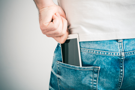 Una mano masculina agarrando un teléfono inteligente en el bolsillo trasero izquierdo de un pantalón de jeans Foto de archivo