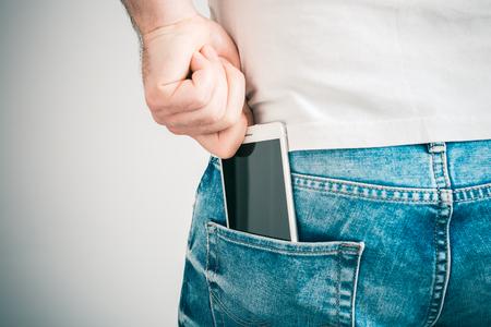 Une main d'homme saisissant un smartphone dans la poche arrière gauche d'un pantalon en jean Banque d'images