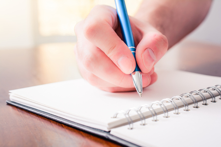 The Front View Of A Male Hand Writing With A Pen In A Blank Book In Front Of A Bright Background