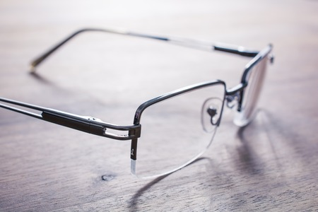 Eyeglasses On Wooden Table With Bright Background Stock Photo