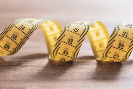 Soft Yellow Measuring Tape in Spiral Shape On A Table Stock Photo