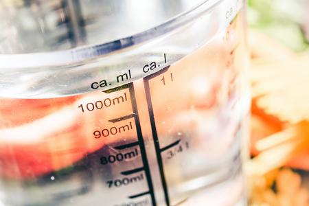 1000 ml - ccm Wasser in einem Messbecher, umgeben von Nudeln, Zwiebeln, Karotten und Gewürzen