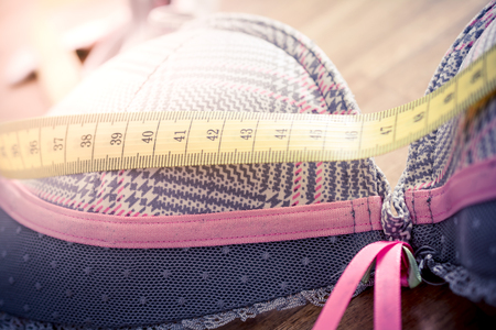Macro Of A Bra With Measuring Tape On Top On A Table - Measure Breast Size Concept 스톡 콘텐츠
