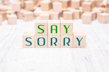 The Words Say Sorry Formed By Wooden Blocks On A White Table