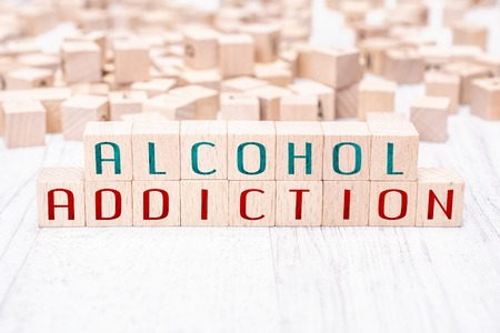 The Words Alcohol Addiction Formed By Wooden Blocks On A White Table Stock Photo