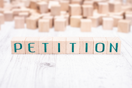 The Word Petition Formed By Wooden Blocks On A White Table Stock Photo