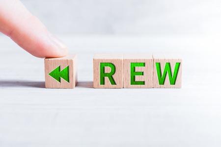 La abreviatura REW formada por bloques de madera y dispuesta por un dedo masculino sobre una mesa blanca
