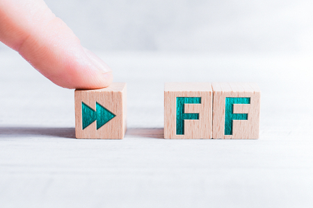 The Abbreviation FF Formed By Wooden Blocks And Arranged By A Male Finger On A White Table