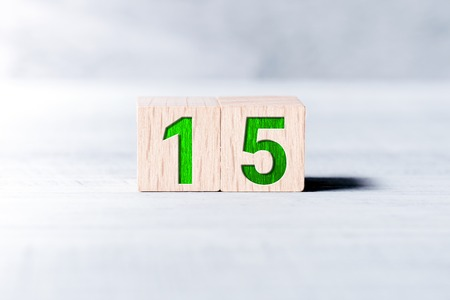Number 15 Formed By Wooden Blocks On A White Table Imagens - 109393435