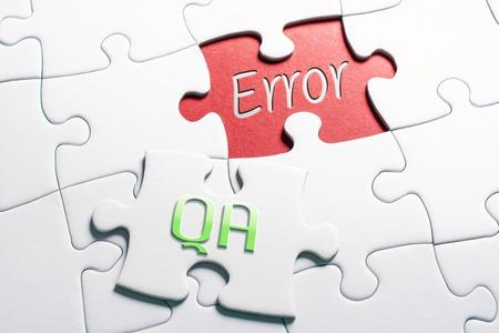 Die Wörter QA und Fehler in fehlendem Puzzleteil Standard-Bild