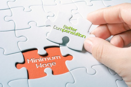 The Words Minimum Wage And Better Compensation In Missing Piece Jigsaw Puzzle 스톡 콘텐츠