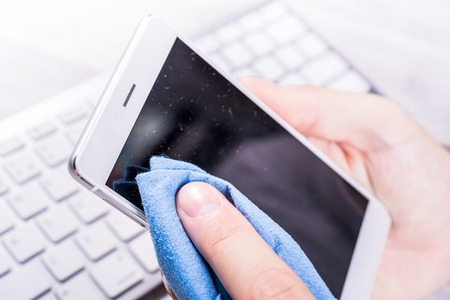 Businessman Cleaning A Smartphone Screen Of Dust, Dirt And Fingerprints With A Cleaning Wipe At His Desk