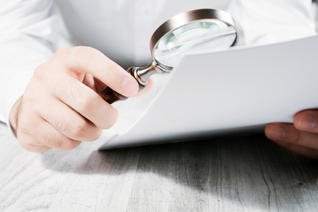 Businessman Analyzing His Documents With A Magnifying Glass