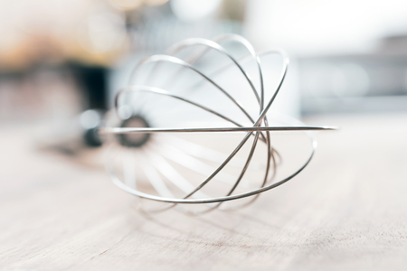 Stainless Whisk On A Wooden Table With Blurred Out Kitchen Background