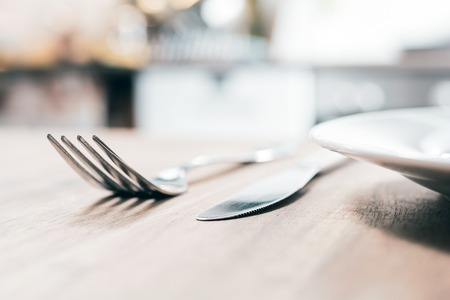 Stainless Fork, Knife And A Ceramic Plate On A Wooden Table With Blurred Out Kitchen Background