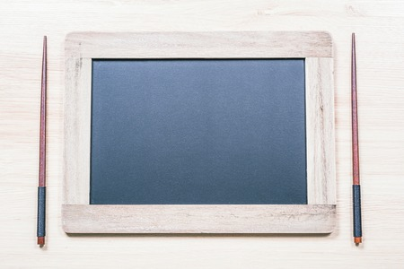 Blackboard With Wooden Frame And Copy Space For A Menu Next To Two Chopsticks