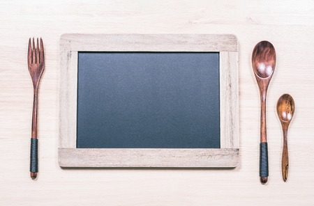 Blackboard With Wooden Frame And Copy Space For A Menu Next To A Wooden Fork And Two Spoons