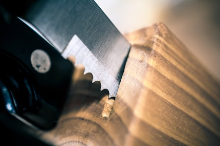 Macro Of A Jagged Steak Knife Partially Pulled Out Of A Kitchen Knive Block On A Table