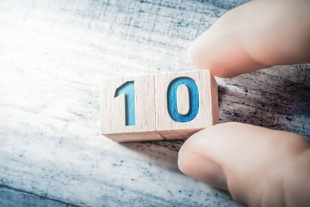 Number 10 Formed By Wooden Blocks And Arranged By Two Male Fingers On A Table Stock fotó