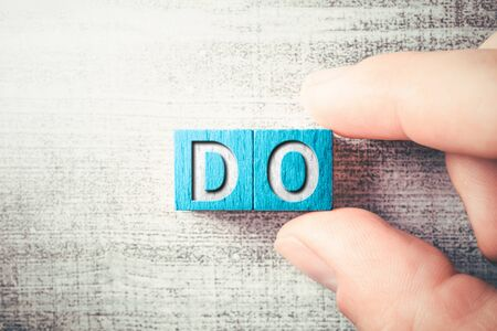 The Word DO On Wooden Blocks And Arranged By Two Male Fingers On A Table
