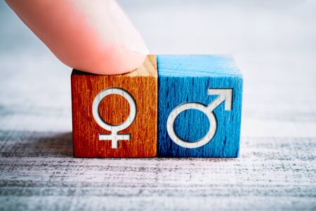 Gender Icon For Female On A Wooden Block Arranged By One Finger Next To The Male Sign On A Table