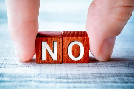 The Word NO On Wooden Blocks And Arranged By Two Male Fingers On A Table