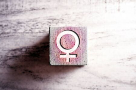 Pink Colored Gender Icon For Female On Wooden Block On A Table Stock fotó