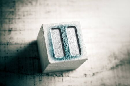 Macro Of A Pause Icon On Wooden Block On A Table
