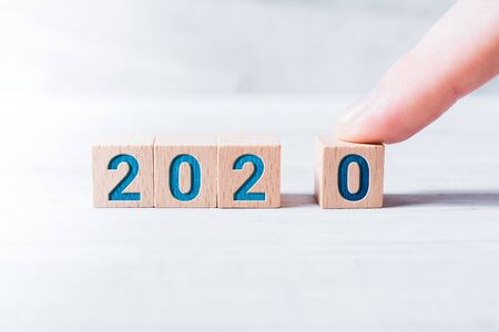 The Year 2020 Formed By Wooden Blocks And Arranged By One Male Finger On A White Table