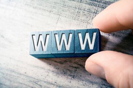 The Word WWW On Wooden Blocks And Arranged By Two Male Fingers On A Table
