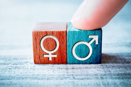 Gender Icon For Male On A Wooden Block Arranged By One Finger Next To The Female Sign On A Table