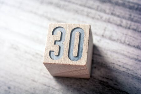 The Number 30 On A Wooden Block On A Table