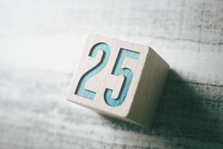 The Number 25 On A Wooden Block On A Table Stock Photo