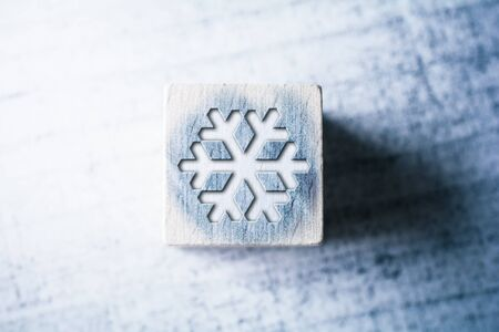 Snowflake Sign On Blue Wooden Block On A Table Stock Photo