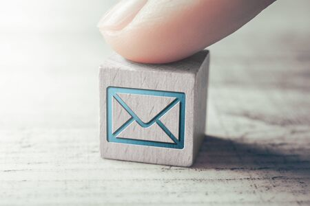 Macro Of An E-Mail Icon On A Wooden Block Arranged By Female Finger On A Table Stock Photo