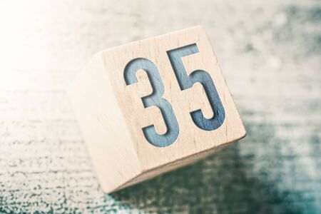 The Number 35 On A Wooden Block On A Table 免版税图像