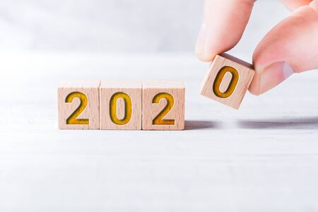 The Year 2020 Formed By Wooden Blocks And Arranged By Male Fingers On A White Table