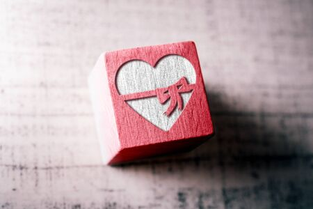 A Heart With A Ribbon Engraved On A Red Wooden Block On A Table Stock Photo