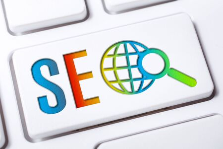 Colorful SEO Search Engine Optimization Button With Globe And Magnifying Glass On A White Keyboard, Business Marketing Concept Stock Photo