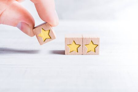 Three Star Ranking Formed By Wooden Blocks And Arranged By A Male Finger On A White Table