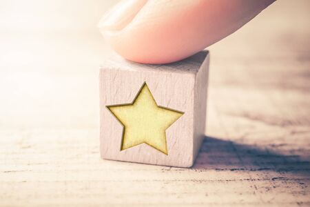 One Star Ranking On A Wooden Block And Arranged By A Male Finger On A Table