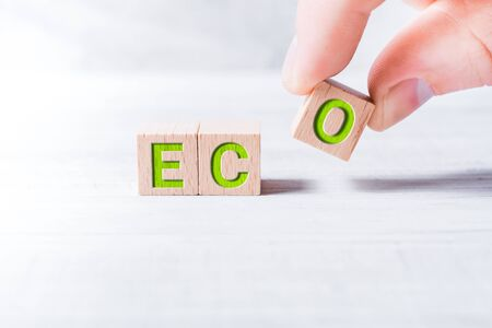 Word Eco Formed By Wooden Blocks And Arranged By A Male Hand On A White Table Stock Photo