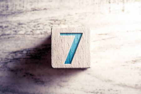 Number 7 On A Wooden Block On A Table Stock Photo