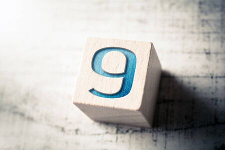 Number 9 On Wooden Block On A Table