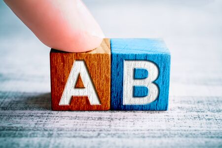 Choice A And B On Wooden Blocks On A Table, One Finger Touches Block A Stock Photo